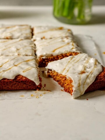 pieces of frosted honey and olive oil oat flour cake