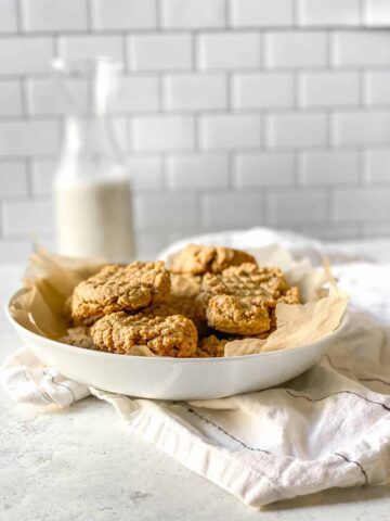 vegan peanut butter cookies in a white bowl on a white and black striped dish towel