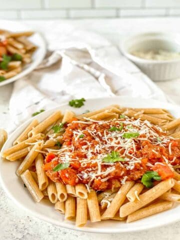 bolognese over penne topped with shredded parmesan cheese