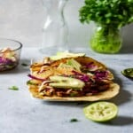 three tacos on a plate behind a lime wedge