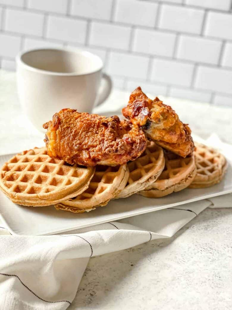 5 waffles on a platter topped with two pieces of fried chicken