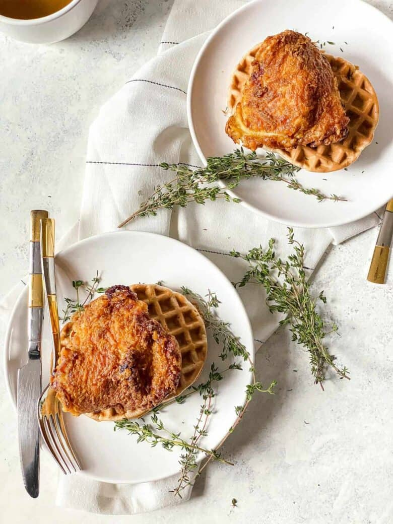 two white plates topped with waffles and air fried chicken with pieces of thyme as garnish