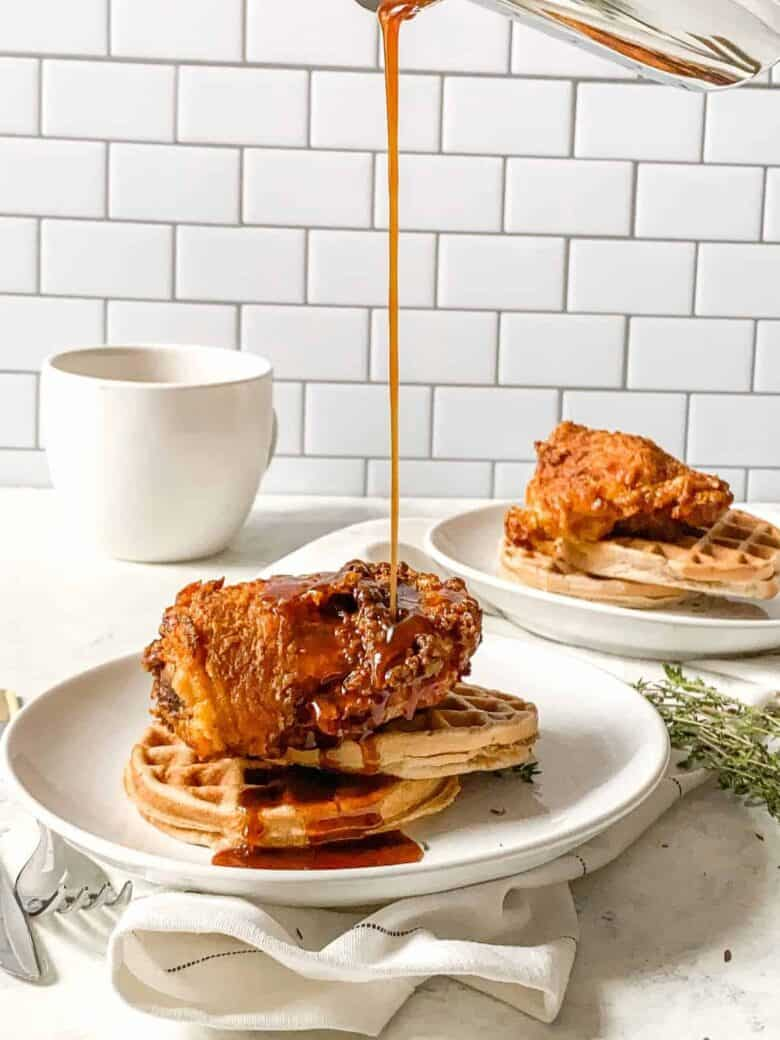 syrup being poured over fried chicken and waffles on a white plate with a white mug in the background