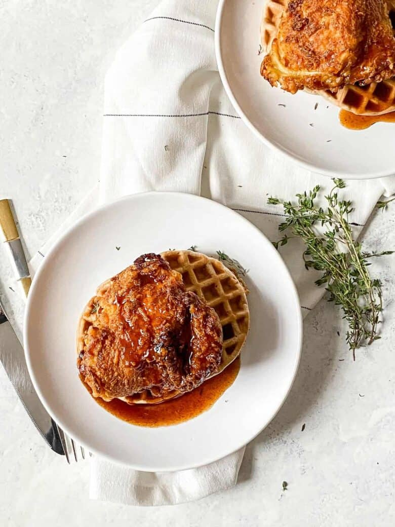 fried chicken and waffles on a small white plate in a pool of syrup