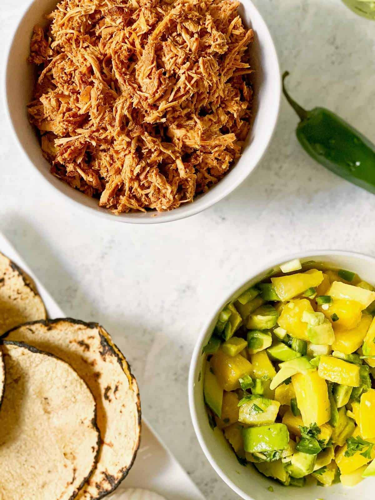 corn tortillas on plate with bbq chicken and pineapple salsa
