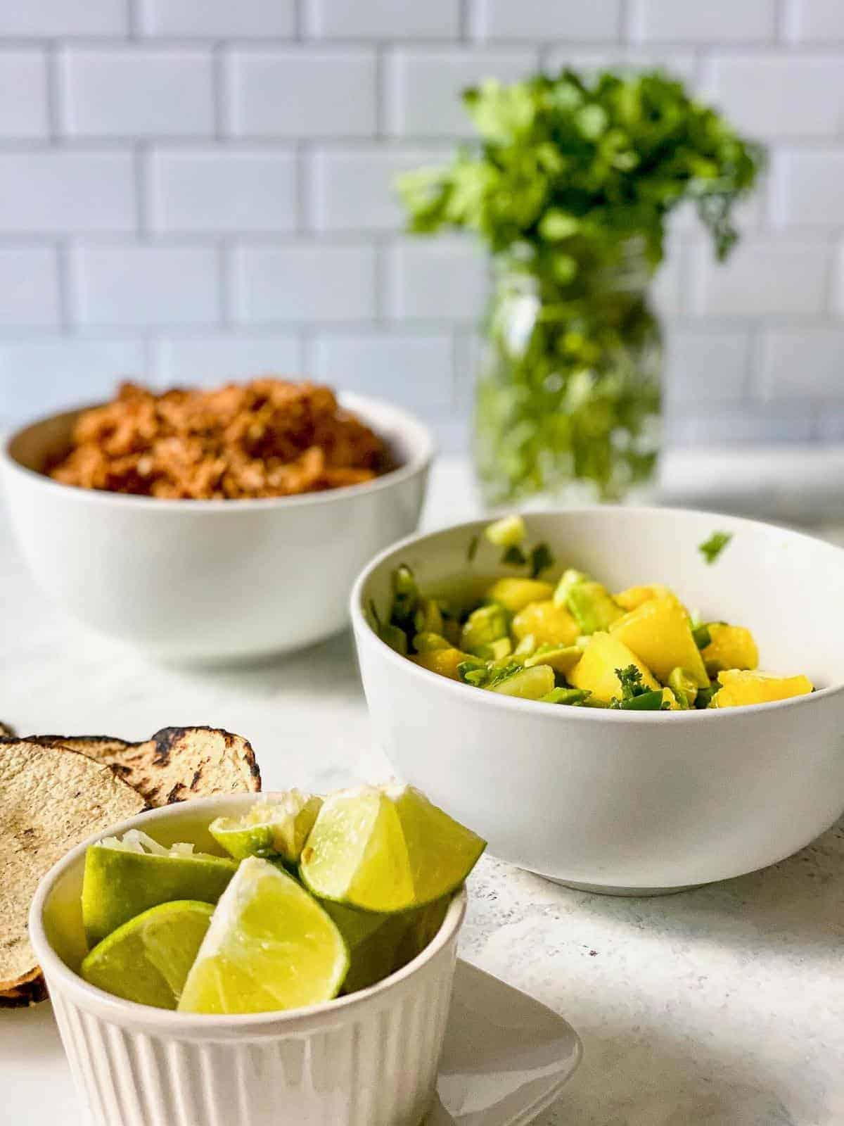 bowl of lime wedges, bowl of pineapple salsa
