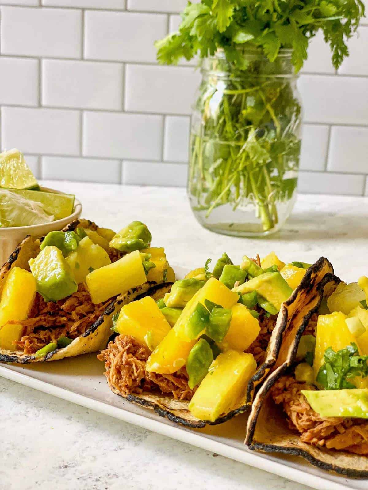 three bbq chicken tacos with pineapple avocado salsa on a plate