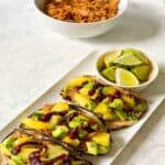 3 tacos with pineapple salsa on plate with bowl of lime wedges