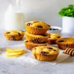three lemon blueberry muffins stacked with other muffins surrounding
