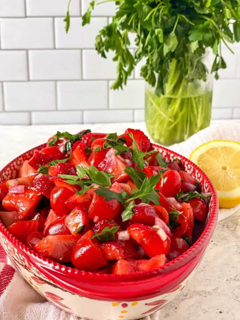 strawberry and tomato salad in a bowl next to parsley