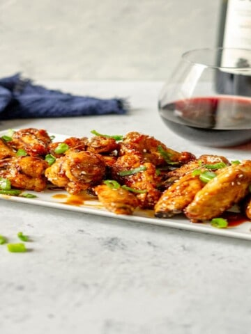 sticky wings topped with sesame seeds and sliced scallions on a white platter in front of a glass of red wine