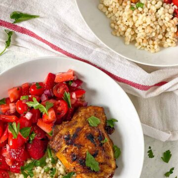 two plates of couscous and tomato salad