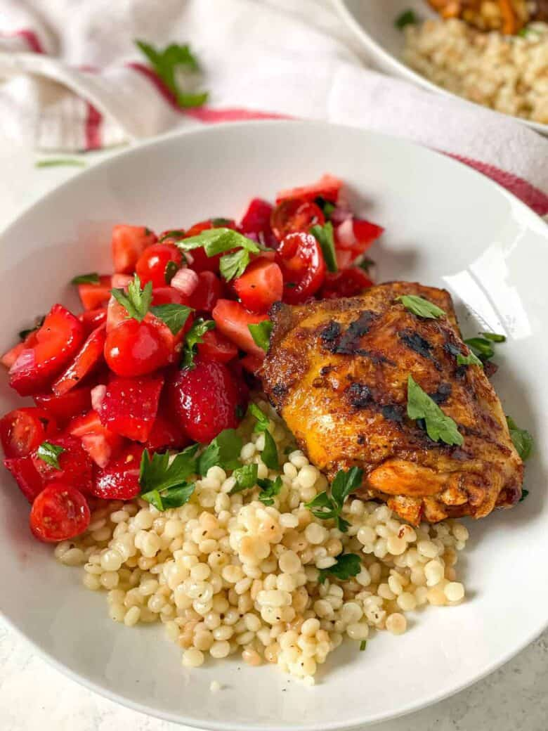 couscous on plate with strawberry tomato salad and chicken