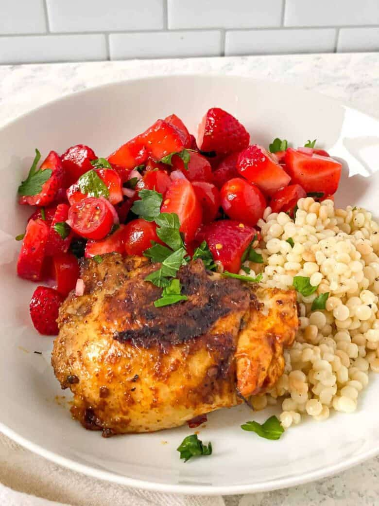 chicken on a plate with strawberry tomato salad and couscous