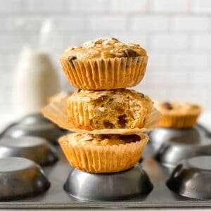 stack of 3 banana oatmeal chocolate chip muffins on an upside down muffin tin