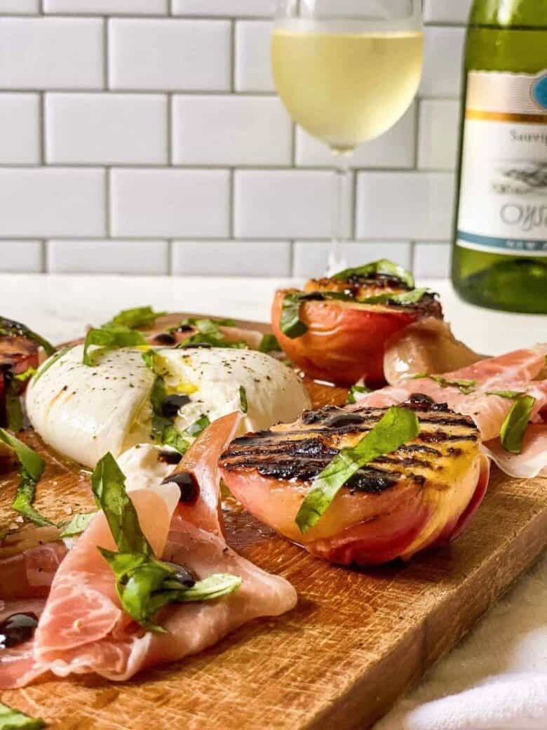 proscuitto and peaches topped with basil on cutting board with glass of white wine