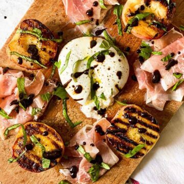 wooden cutting board topped with cheese, peaches and cured meat