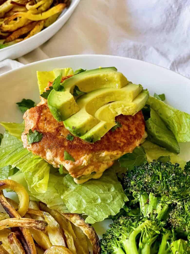 salmon burger and sliced avocado