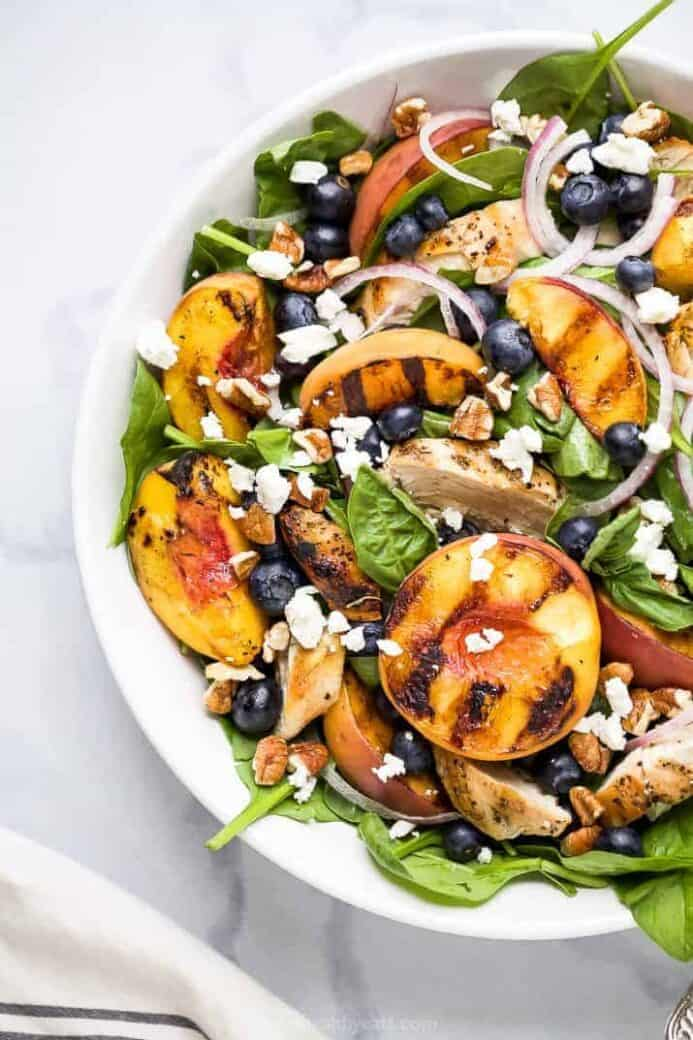 grilled peaches over spinach in a bowl