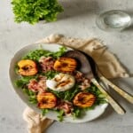 grilled peach, burrata and prosciutto salad on a white platter on top of a tan linen napkin and next to a glass of water