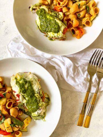 pesto mozzarella chicken with vegetable pasta on 2 plates