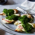 four chicken breasts topped with tomato, mozzarella and pesto on a platter with a pair of tongs