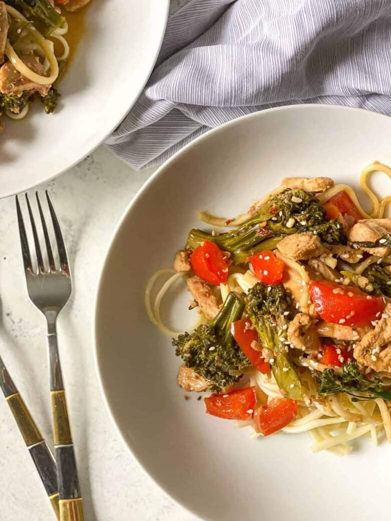 chicken, broccoli and pepper noodle stir fry on white bowls