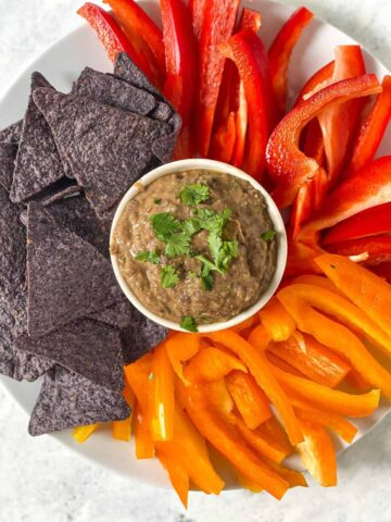 tortilla chips and bell peppers surrounding a bowl of bean dip