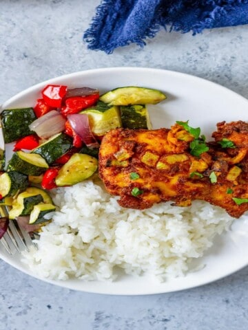 curry chicken thigh on a plate with roasted vegetables and white rice