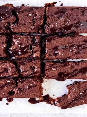 brownies cut into squares and drizzled with melted chocolate and sea salt on wax paper