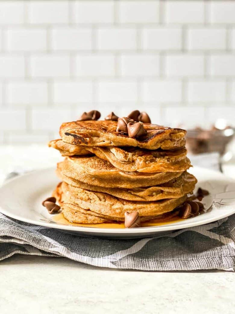 whole wheat banana pancakes stacked on a white plate topped with syrup and chocolate chips