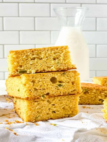 3 pieces of jalapeno cornbread stacked with a jar of milk in the background
