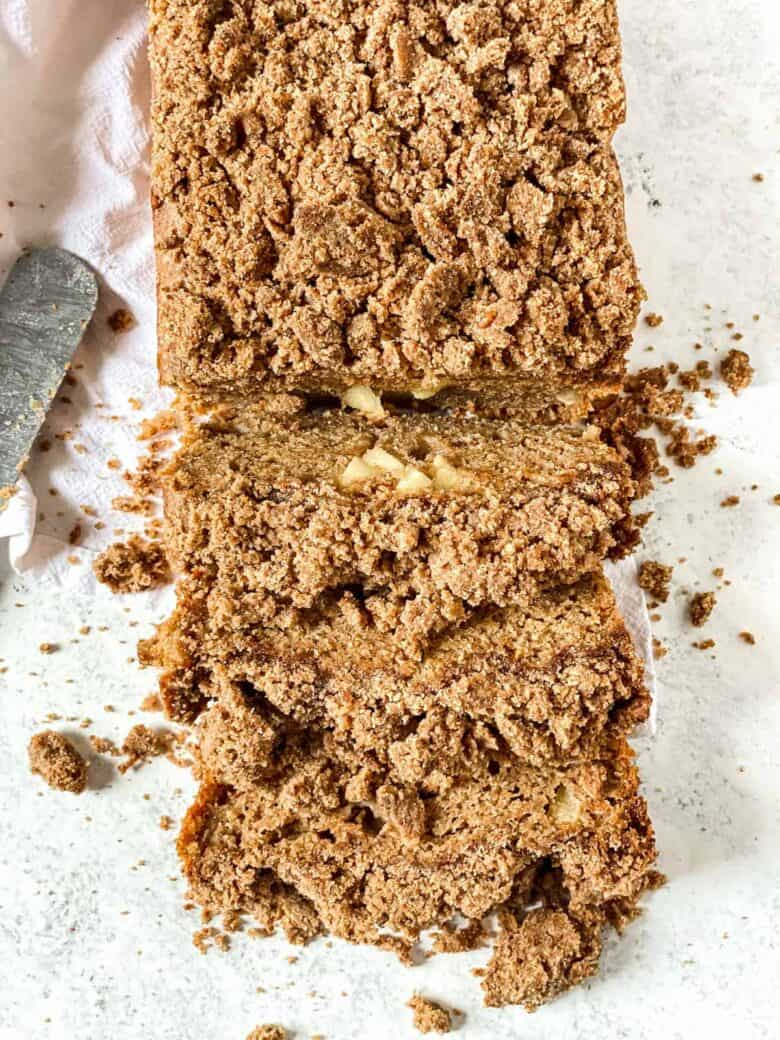 loaf of apple bread with crumb topping with 3 slices cut