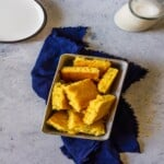 pieces of cheddar jalapeño cornbread in a silver baking pan on a blue linen
