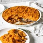 a plate of ground beef, vegetables and mashed sweet potatoes with the casserole behind it