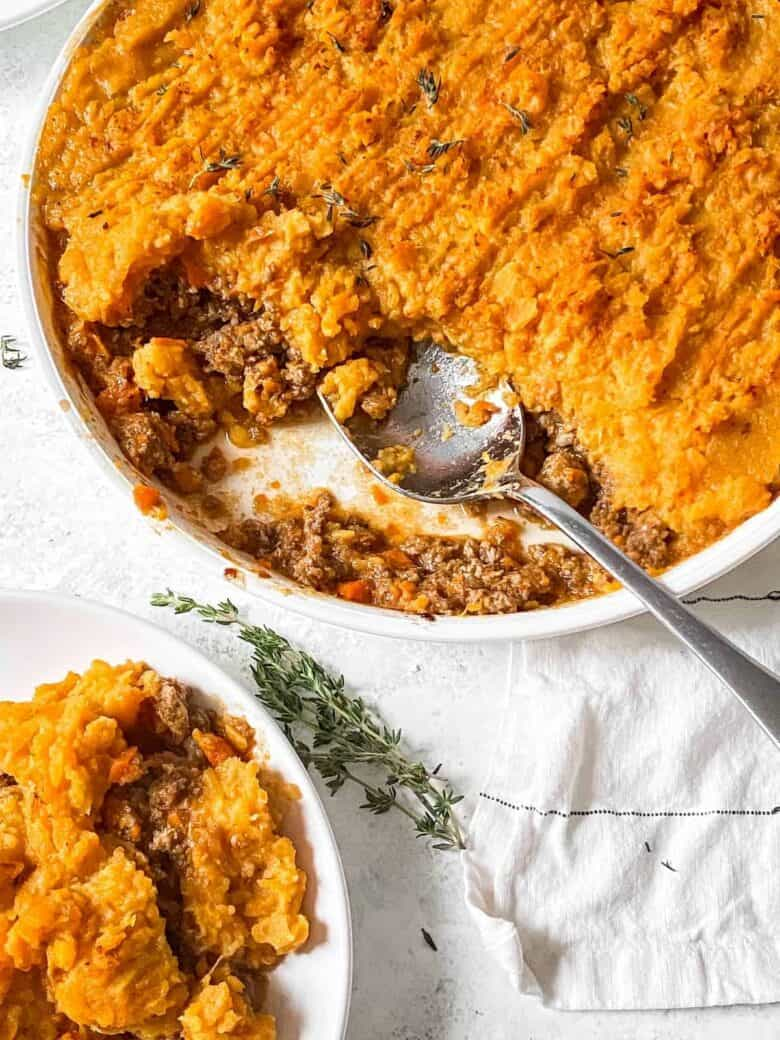 one serving of sweet potato shepherd's pie on a white plate next to the casserole