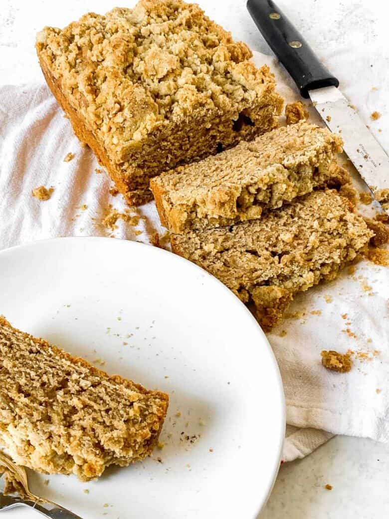 slice of coffee cake on a small white plate next to the entire loaf