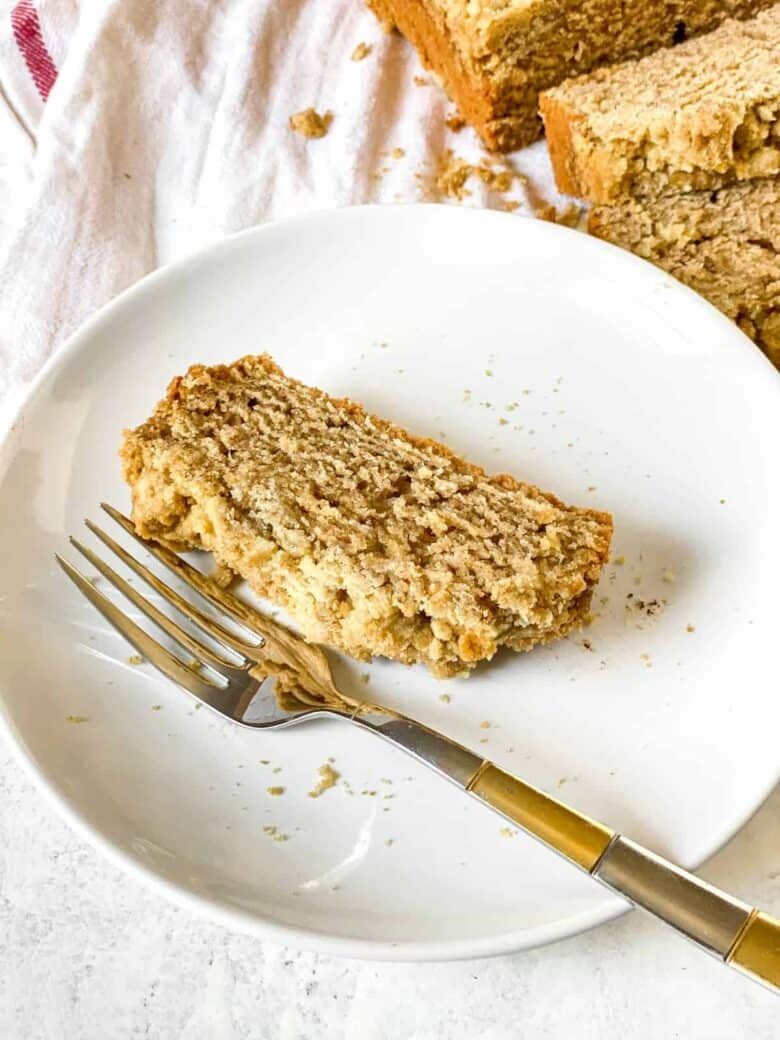 slice of coffee cake on a white plate with a gold and silver fork