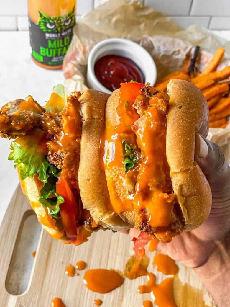 2 buffalo chicken sandwiches being held up sideways