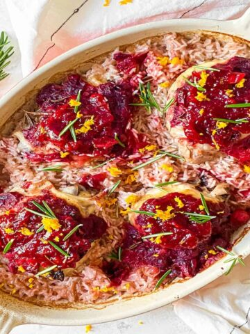 chicken thighs topped with cranberry sauce in a baking dish