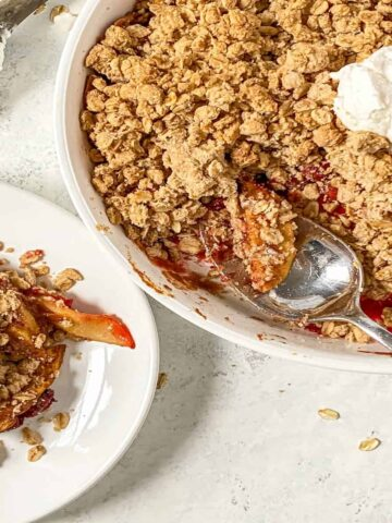 apple crisp in a pie dish with a scoop of vanilla ice cream and some scooped onto a plate