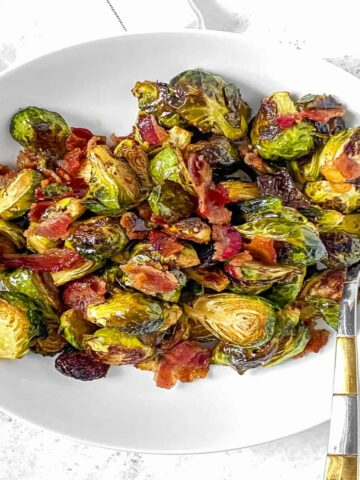 brussels sprouts in a white bowl with bacon pieces