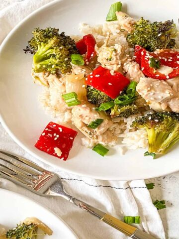 chicken, broccoli and red peppers over white rice on a plate