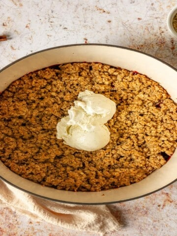 apple and cranberry crisp topped with vanilla ice cream in a dutch oven
