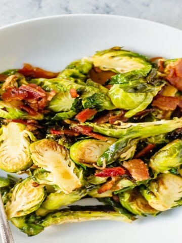white dish filled with brussels sprouts and bacon