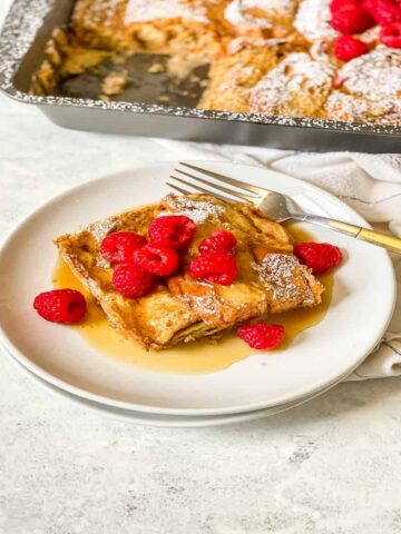 piece of french toast topped with fresh raspberries and maple syrup on a white plate with a gold and silver fork