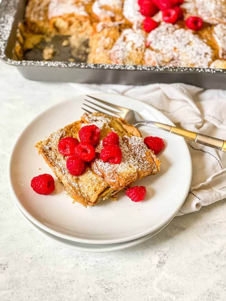 piece of french toast topped with fresh raspberries on a white plate with a gold and silver fork