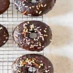 chocolate sprinkle donuts on a cooling tray