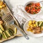 sheet pan with zucchini and potatoes and a bowl of bruschetta