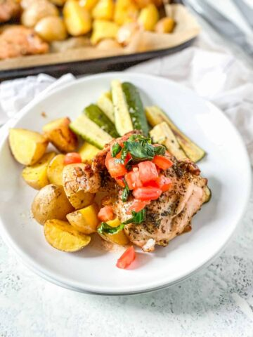 balsamic chicken thigh topped with bruschetta on a white plate with yellow potatoes and sliced zucchini